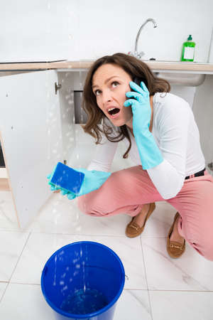 Young Woman Calling To Plumber Through Mobile Phone While Leakage Water Falling Into Bucket Stock Photo