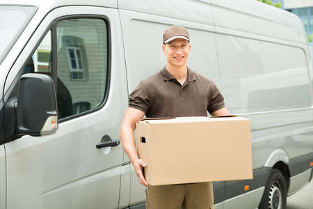 courier man: Happy Delivery Man Holding Box In Front Van