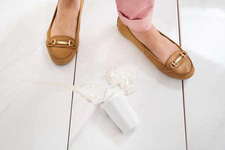 trouser legs: Close-up Of Female Leg Wearing Brown Footwear Standing Near The Yoghurt Spilled On Floor