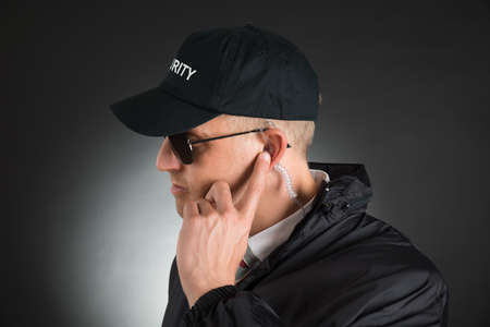 earpiece: Secret Service Agent Listening To Earpiece Over Black Background