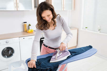 the iron lady: Happy Woman Ironing Trousers With Electric Iron At Home