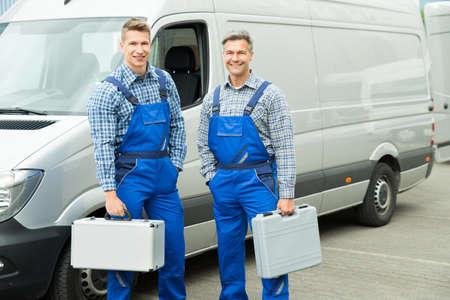 fontanero: Joven trabajador de sexo masculino feliz con caja de herramientas se coloca delante de Van Foto de archivo