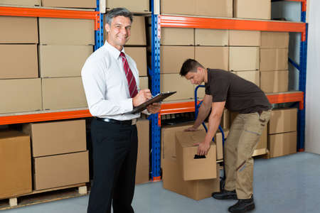 two men: Happy Manager Writing On Clipboard While Worker Carrying Box In Warehouse Stock Photo