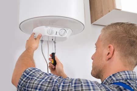 MÅ,ody Mę żczyzna Pracownik Mocowanie Elektryczne Boiler With Screwdriver Zdjęcie Seryjne