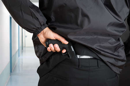 security uniform: Close-up Photo Of Bodyguard Hands Removing Handgun