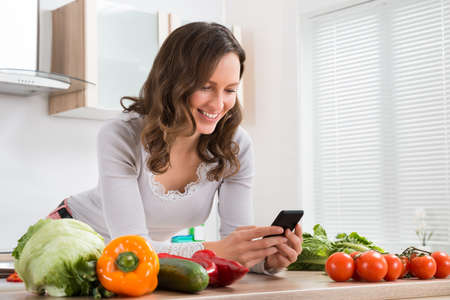 Young Woman With Vegetables Smiling While Using Mobile Phone In Kitchen