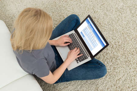 Young Woman Sitting On Carpet With Laptop Filling Survey Form 版權商用圖片