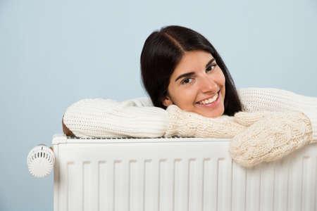 라디에이터에 기대어 스웨터에 젊은 행복한 여자