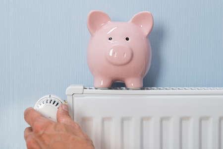 strom: Close-up der menschlichen Hand einstellen Thermostat mit Sparschwein auf Kühler