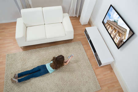 lying on couch: High Angle View Of Girl Lying On Carpet Watching Television At Home Stock Photo