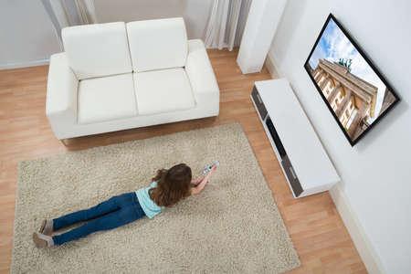 viendo television: Opini�n de alto �ngulo que miente en la alfombra que miran la televisi�n en el hogar