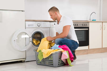wash machine: Young Handsome Man Putting Dirty Clothes Into The Washing Machine At Home