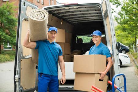 Zwei männliche Arbeitnehmer tragende Teppich-und Kartonkästchen vor Van