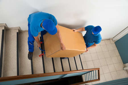 parcel service: Two Male Movers Walking Downward With Box On Staircase