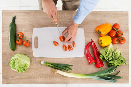 chopping: High Angle View Of Male Hands Chopping Vegetables In Kitchen Stock Photo