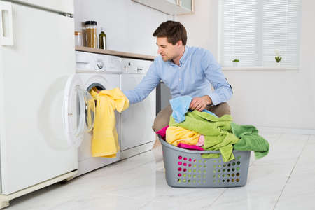 machine: Young Man Loading Clothes Into Washing Machine In Kitchen