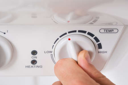 Close-up van de persoon die handen draaien de knop van Electric Boiler