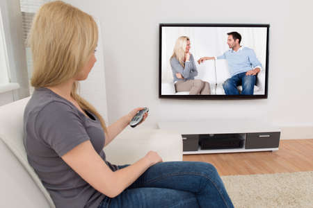 Young Woman Changing Channel With Remote Control In Front Of Television photo