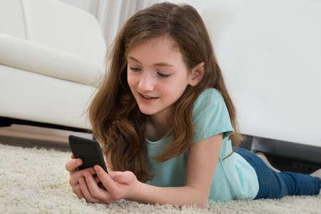 niños felices: Niña feliz con el teléfono móvil acostado alfombra en la sala de estar