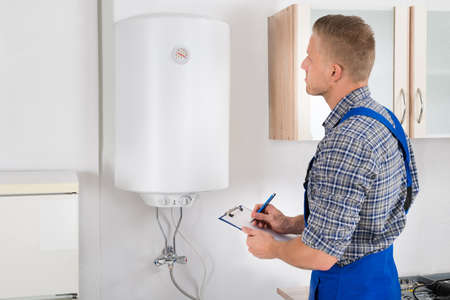 installations: Young Man Writing On Clipboard While Looking At Electric Boiler Stock Photo