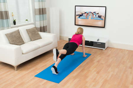 doing: Young Woman Doing Workout While Watching Television In House Stock Photo