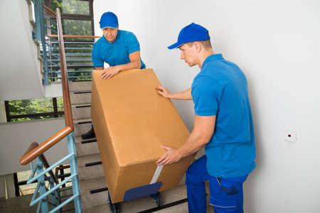 Twee Man Movers Wandelen Neerwaartse met doos op een Trap