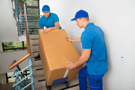 house moving: Two Male Movers Walking Downward With Box On Staircase
