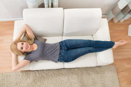 lying on couch: Young Happy Woman Lying On White Sofa At Home