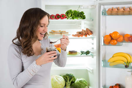 refrigerador: Mujer joven que come delante de la nevera en la cocina
