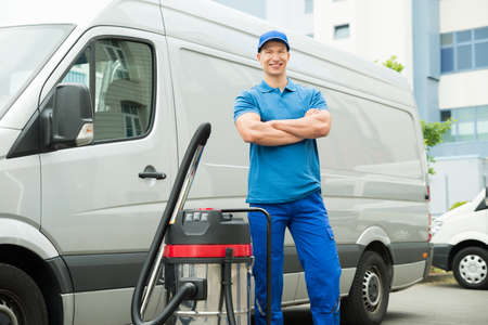 man at work: Happy Male Cleaner In Blue Uniform Standing With Vacuum Cleaner