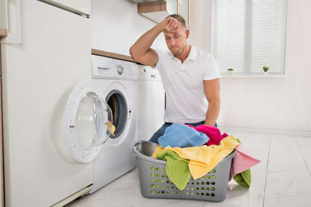 unhappy man: Tired Young Man Loading Clothes Into The Washing Machine At Home Stock Photo