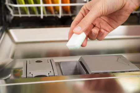 scour: Close-up Of Person Hands Putting Dishwasher Soap Tablet In Detergent Dishwasher Box