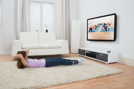 Girl Exercising On Carpet While Watching Television In Living Room photo