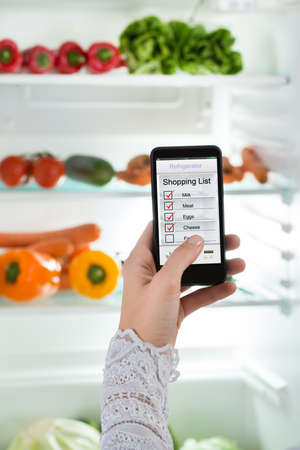 convenience store: Close-up Of Person Hand With Mobile Phone Showing Shopping List On Display Stock Photo