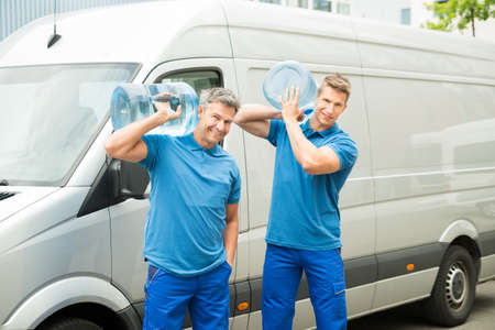 gallon: Two Delivery Men In Front Of Cargo Van Delivering Bottles Of Water Stock Photo