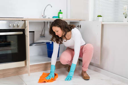 floor cloth: Young Woman Wiping Floor With Cloth In Kitchen