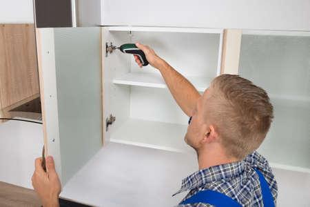 menuisier: Homme Carpenter forage dans Cabinet avec une perceuse électrique sans fil