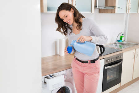 detersivi: Giovane Donna Felice di versamento liquido detergente In Bottle Cap