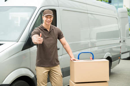 delivery truck: Young Delivery Man In Front Van With Cardboard Boxes Showing Thumbs Up Sign