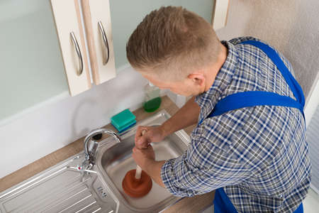 cleaning tools: High Angle View Of Worker Pressing Plunger In Steel Kitchen Sink Stock Photo