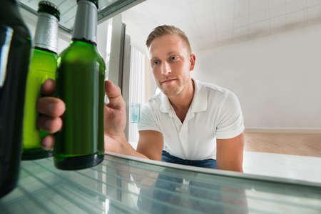 refrigerador: Hombre joven que toma la botella de cerveza de un refrigerador en el hogar Foto de archivo