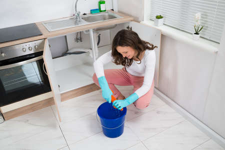 leakage: Young Woman Squeezing Wet Rag In Blue Bucket At Kitchen Room