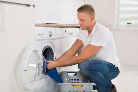 man laundry: Man With Laundry Basket Loading Washing Machine With Clothes In Kitchen Room