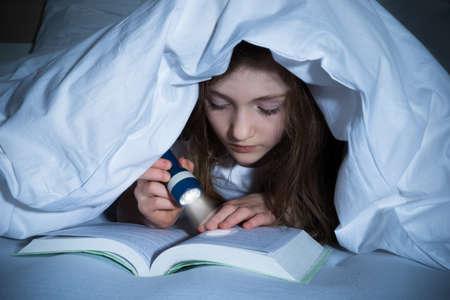 女の子のベッドの上は、毛布の下に懐中電灯で本を読んで