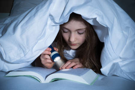 Girl Reading Book With Flashlight Under The Blanket On Bed