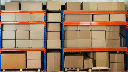 warehouse equipment: Cardboard Boxes On Shelves In Distribution Warehouse