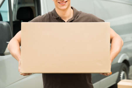 man carrying box: Close-up Of Young Delivery Man Carrying Box In Hand