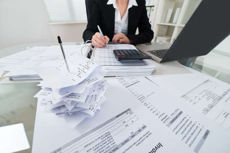 Close-up Of Businesswoman Calculating Tax With Calculator And Laptop At Desk