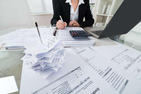 contabilidad: Primer De La Empresaria Impuesto Calculando con la calculadora y la computadora port�til en el escritorio Foto de archivo