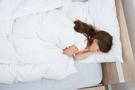 cama: Vista elevada de la muchacha que duerme en cama en el dormitorio